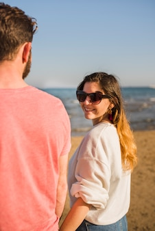 Smiling young woman standing with her boyfriend wearing sunglasses looking over shoulder at beach