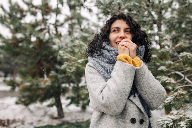 Smiling young woman stands in a frosty snowy winter park.