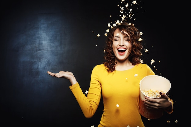 Smiling young woman staying under popcorn shower with right hand up