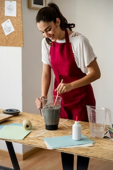 Smiling young woman stirring paper pulp in blender