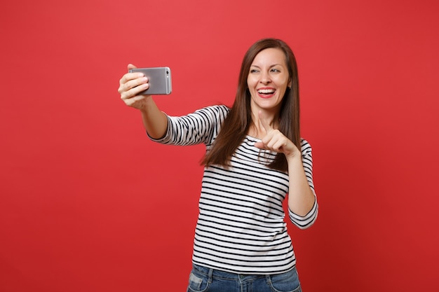 Smiling young woman in striped clothes doing taking selfie shot on mobile phone pointing index finger isolated on bright red background. people sincere emotions, lifestyle concept. mock up copy space.