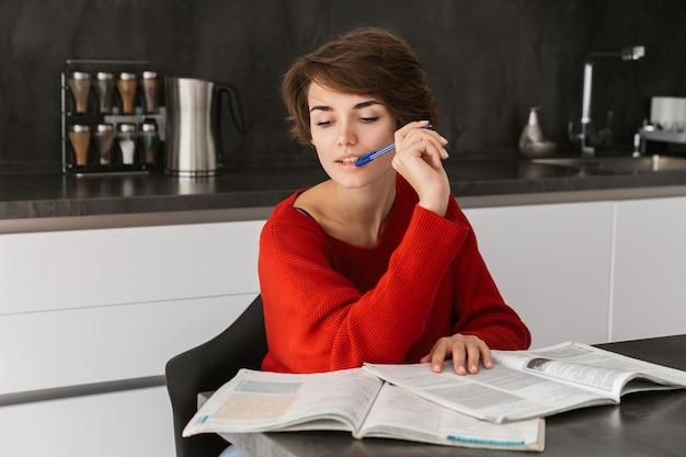 Улыбающаяся молодая женщина учится за столом на кухне дома