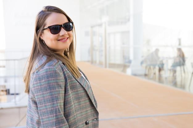 Giovane donna sorridente in occhiali da sole che esaminano macchina fotografica