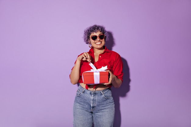 La giovane donna sorridente in occhiali da sole con bordo rosso, in orecchini d'oro rotondi e in maglietta rossa si rallegra del suo dono sul lilla.