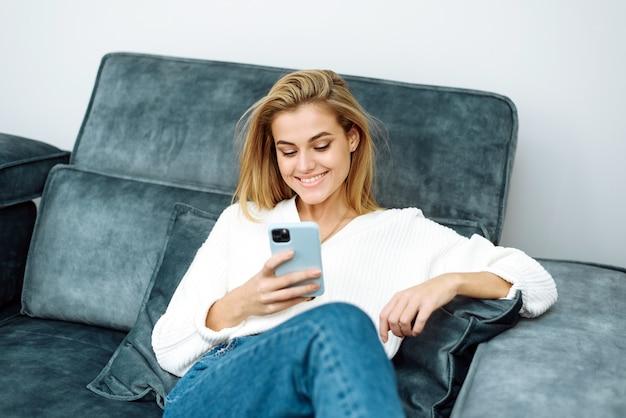 Улыбающаяся молодая женщина, занимающаяся серфингом в интернете и покупающая вещи, сидя на диване у себя дома.
