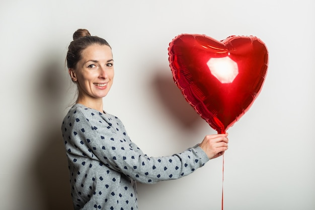 Smiling young woman in a sweater holding a heart air balloon on a light background. valentine's day concept. banner.