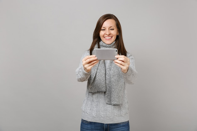 Smiling young woman in sweater scarf doing selfie shot on mobile phone making video call isolated on grey background. healthy fashion lifestyle people emotions cold season concept. mock up copy space.