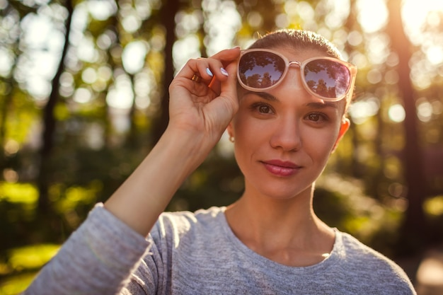 Smiling young woman taking off her sunglasses in park
