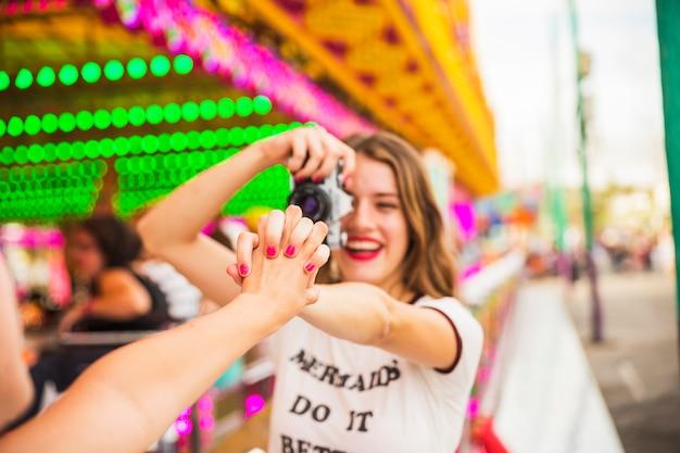 彼女の友人の手を持ってカメラから写真を撮る若い女性に笑顔