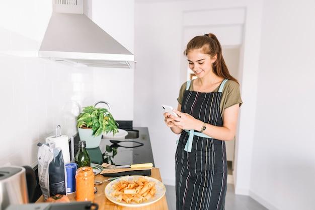 Улыбается молодая женщина, сфотографировать приготовленное блюдо макароны на мобильный телефон