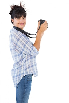 Smiling young woman taking picture with her camera