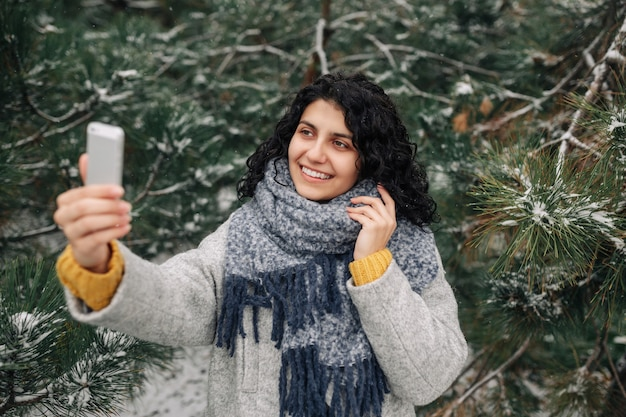 Smiling young woman taking selfie at the snowy winter park. happiness concept.