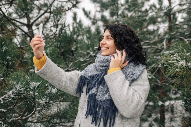 Smiling young woman taking selfie at the snowy winter park.