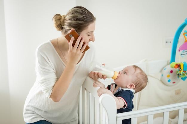 Улыбающаяся молодая женщина разговаривает по телефону во время кормления своего маленького сына