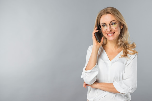 Smiling young woman talking on mobile phone against gray backdrop