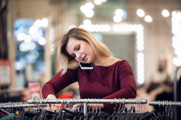 Smiling young woman talking on a mobile phone while shopping in a retail store