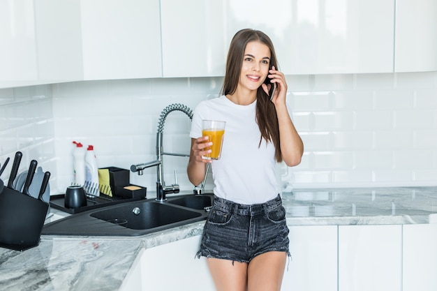 Smiling young woman talking on mobile phone while standing on a kitchen with glass of juice
