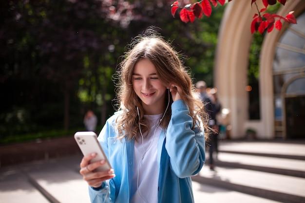 Улыбающаяся молодая женщина разговаривает по видеосвязи на смартфоне с наушниками в центре города