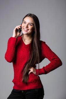 흰 벽에 빈 복사본 공간을 올려 휴대 전화에 말하는 젊은 여자를 웃고