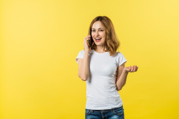 노란색 배경으로 핸드폰에 말하는 젊은 여자를 웃 고