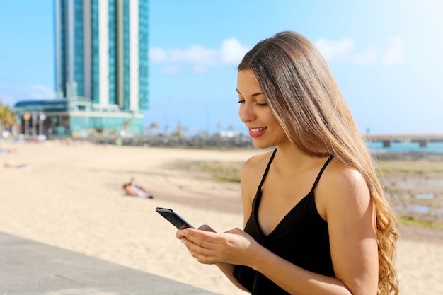 Smiling young woman in tank top texting