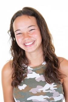 Улыбается девушка-подросток в армейской рубашке на белом фоне