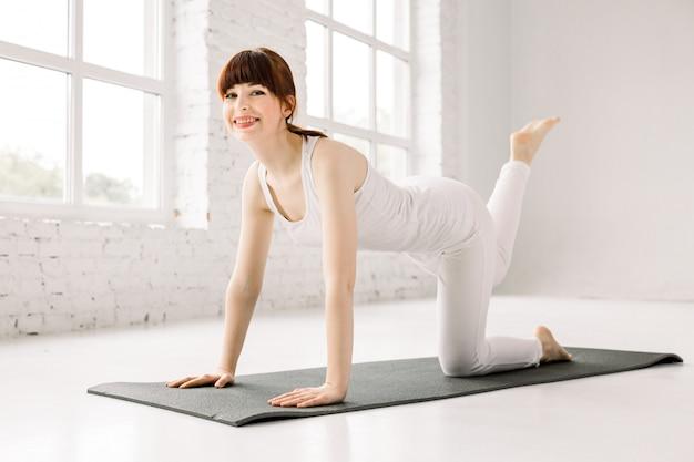 ジムでマットの上の若い女性トレーニング脚を笑っています。ヨガの練習、ドンキーキックのエクササイズ、ワークアウト、スポーツウェア、ヨガスタジオを着ている女性