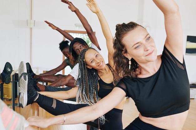 Улыбающаяся молодая женщина тренируется с друзьями и наклоняется к ноге на балетной тяге