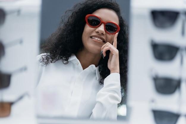 Улыбающаяся молодая женщина примеряет солнцезащитные очки в магазине оптометрии