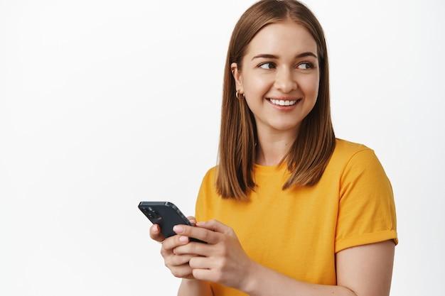 笑顔の若い女性はスマートフォンを使用し、携帯電話のモバイルアプリを保持し、幸せそうな顔で肩の後ろに頭を向け、白い壁に黄色のtシャツで立っています
