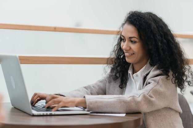 Улыбающаяся молодая женщина с помощью ноутбука, сидя за столом в кафетерии