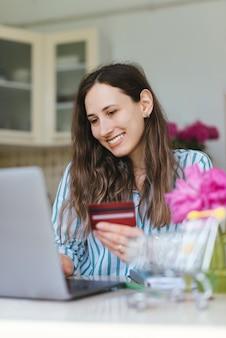 Улыбается молодая женщина с помощью кредитной карты и покупки что-то онлайн