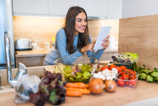 Smiling young woman using digital tablet with vegetable on countertop in kitchen