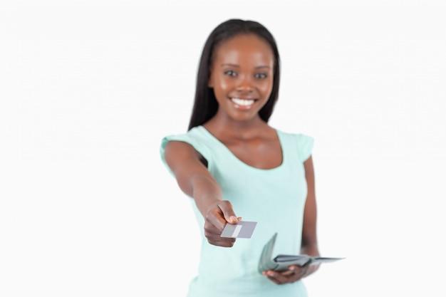 Улыбается молодая женщина, используя ее кредитной карты для оплаты