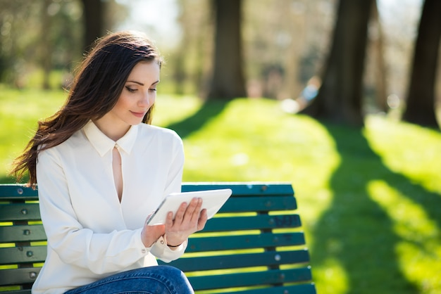 Smiling young woman using her tablet in a park