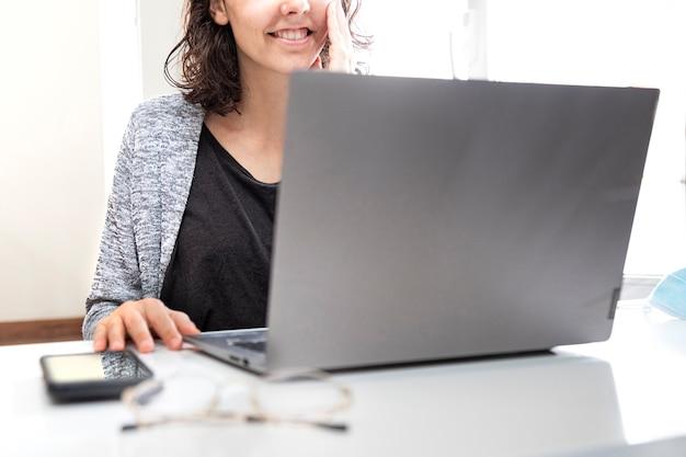 Улыбающаяся молодая женщина, использующая ноутбук дома для удаленной работы работа из дома концепции