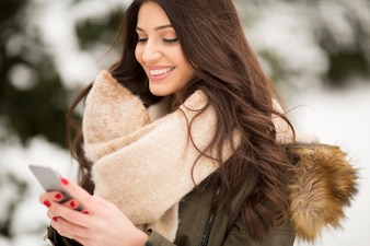 Smiling young woman using phone in park at cold winter day