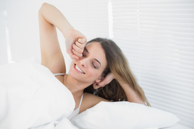 Smiling young woman waking up lying in her bed