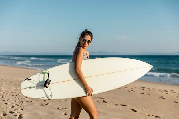 Smiling young woman walking with surfboard on seashore