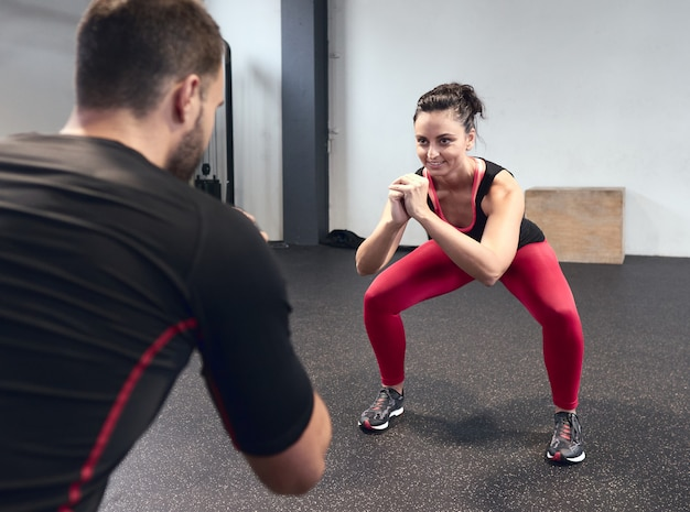 Smiling young woman warming up with her personal trainer at the gym