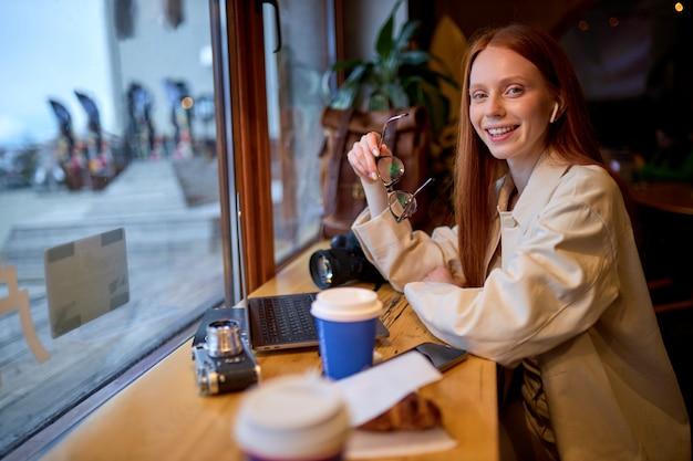 현대적인 노트북 장치에서 온라인 튜토리얼을 보고 있는 웃고 있는 젊은 여성