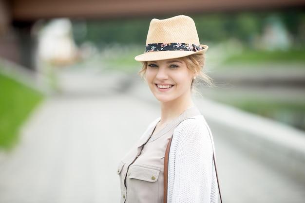 젊은 여자는 모자를 쓰고 웃 고