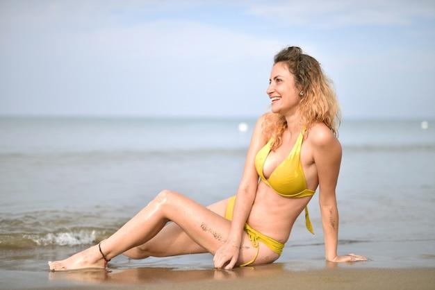 ビーチで水着を着て笑顔の若い女性-幸福の概念
