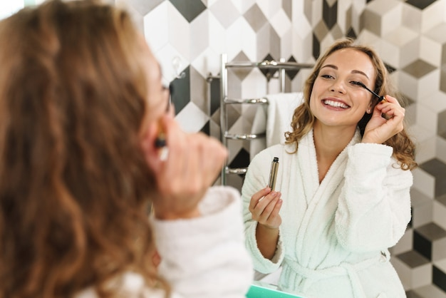バスルームの鏡に立って、マスカラを適用しながら、バスローブを着て化粧をしている若い女性の笑顔