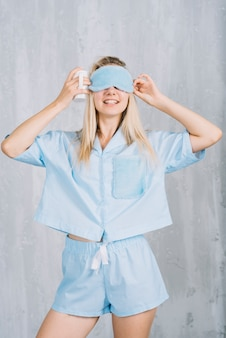 Smiling young woman wearing blue sleeping eye mask against wall