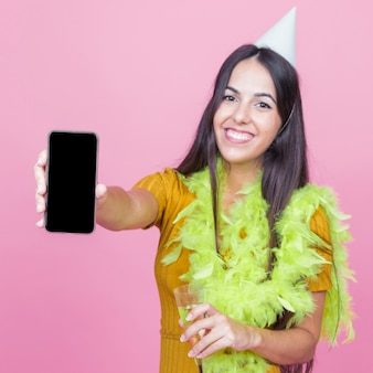 Smiling young woman wearing boa and party hat showing smartphone