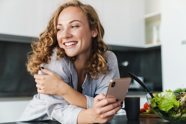 台所のテーブルに寄りかかって携帯電話を使用してカジュアルな服を着て笑顔の若い女性