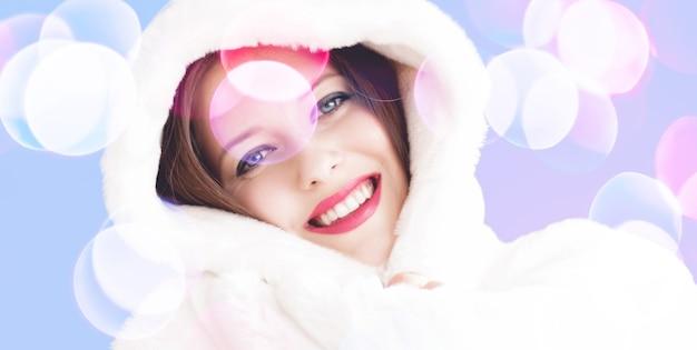 Улыбающаяся молодая женщина в пушистой белой шубе