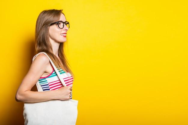 안경을 쓰고 웃는 젊은 여자는 그녀의 어깨에 린넨 가방을 보유하고 있습니다.