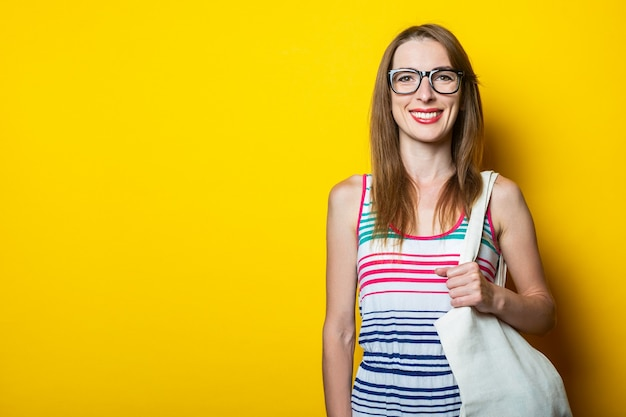 Smiling young woman wearing glasses holds linen bag on shoulder on yellow background.